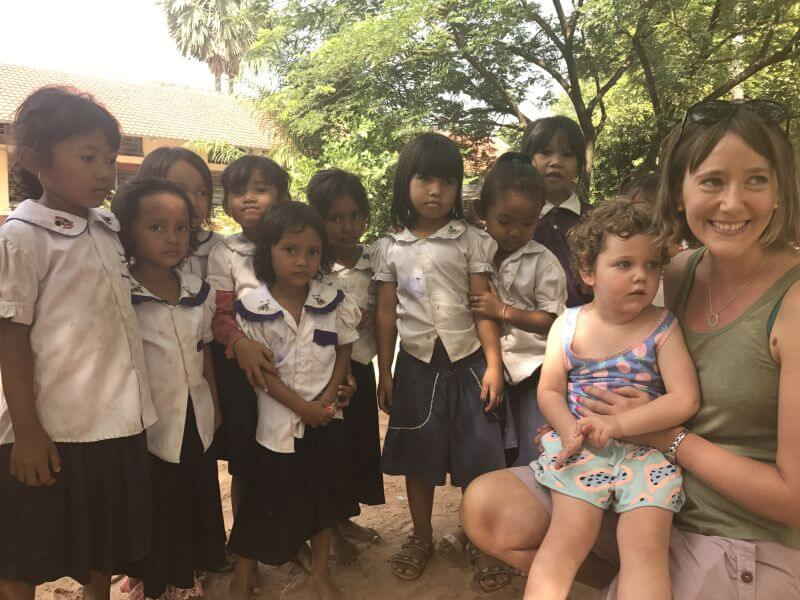 Amber and Olive from HIll Tribe Travels standing with a group of school kids on our temple alternative tour with Dani from Bees Unlimited