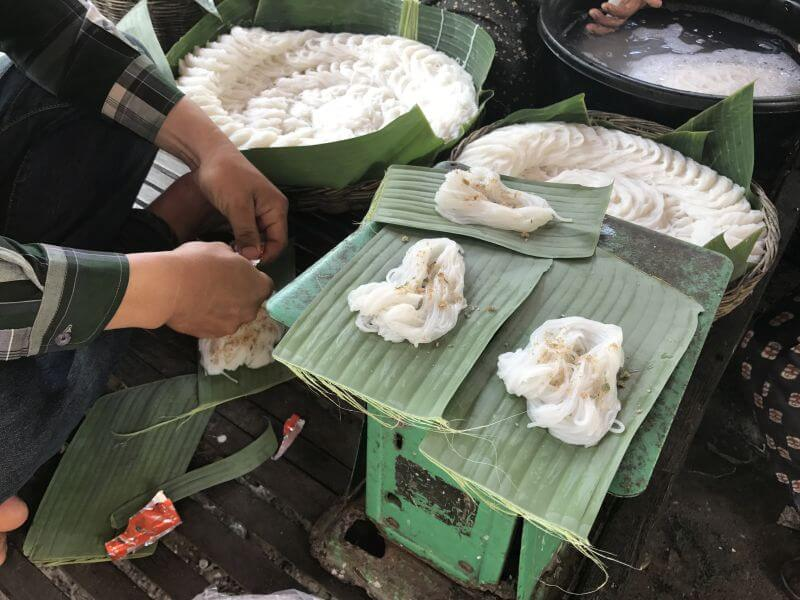 Noodles being prepared and place onto big leaves. Hill Tribe Travels stopped and watched the family making the noodles on temple alternative tour with Dani from Bees Unlimited