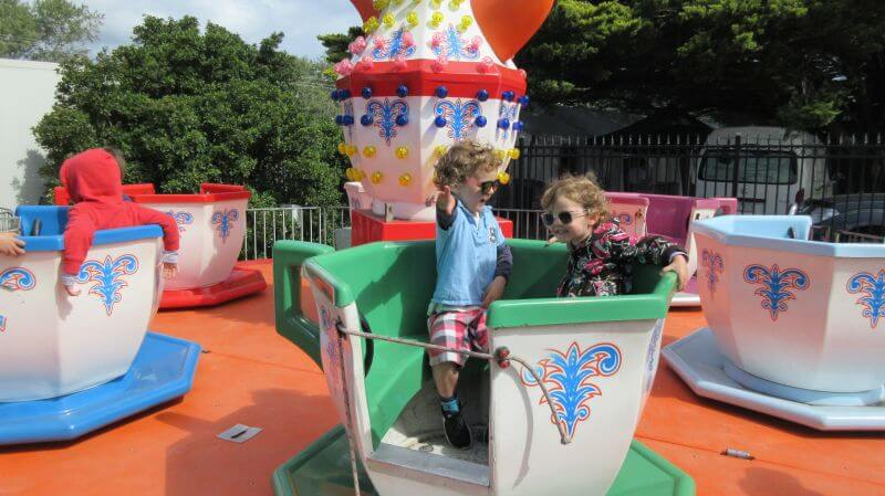 Ned and Olive from Hill Tribe Travels enjoying the tea cups ride at The Peninsula Picnic