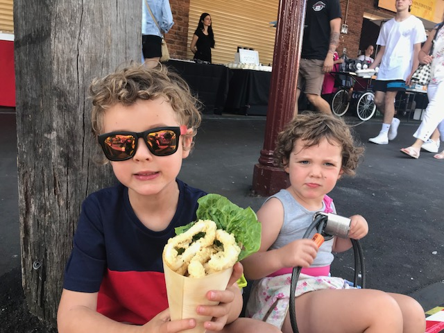 Ned and Olive sitting at the South Melbourne Night Market enjoying the delicious calamari