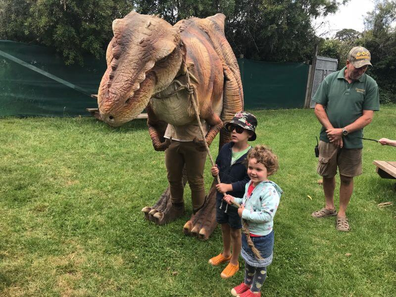 Ned and Olive from HIll Tribe Travels holding onto the lead of Wilson the walking dinosaur at Dinosaur World Somerville
