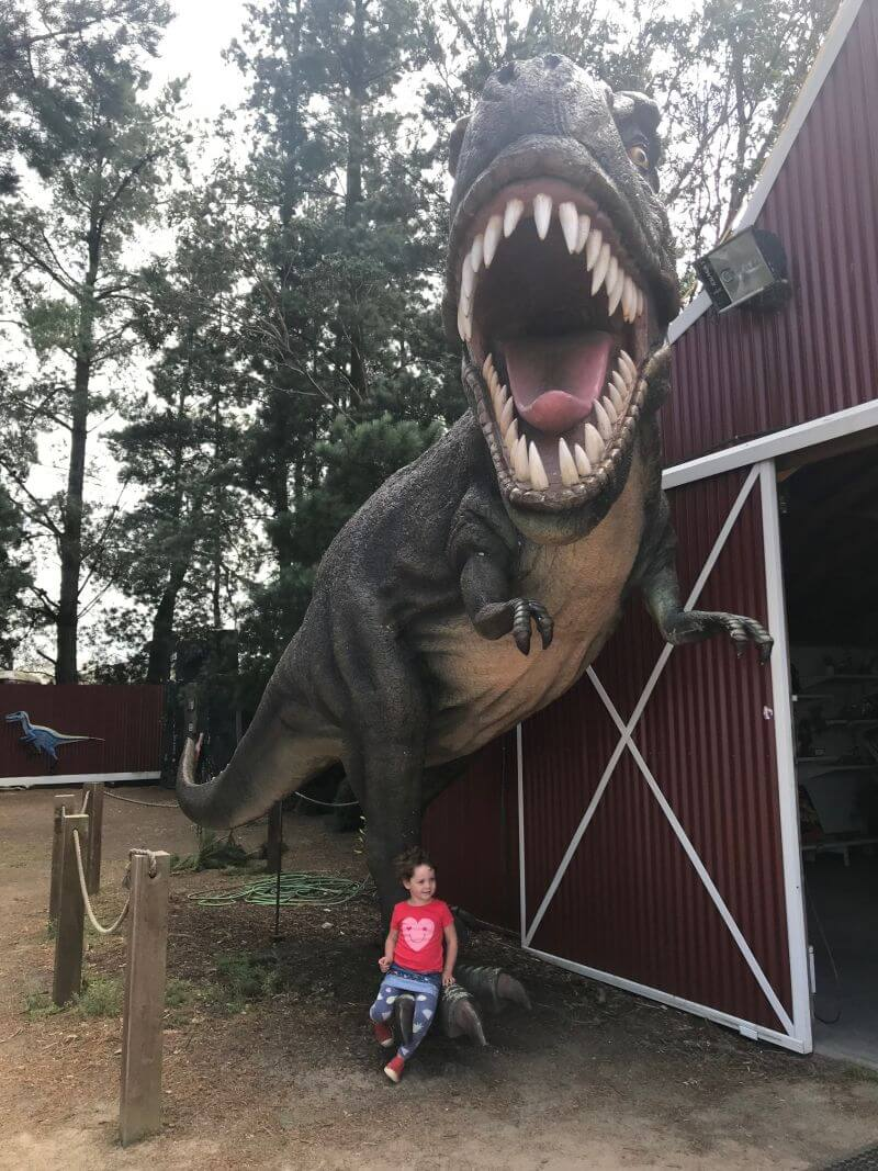 Olive from Hill Tribe Travels sitting under the T-Rex at the entrance to Dinosaur World, Somerville