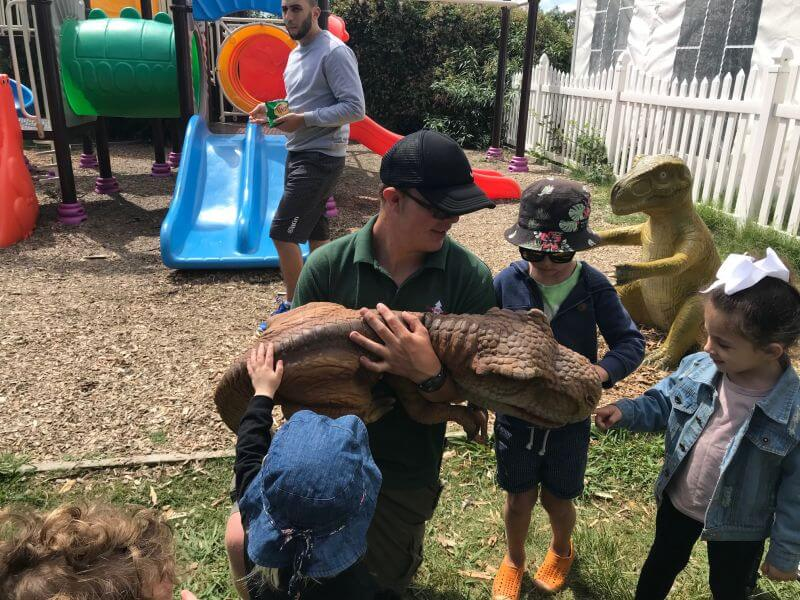 Dinosair keeper bending down with a dinosaur puppet for the kids to have a pat and ask questions - Hill Tribe Travels kids loved this