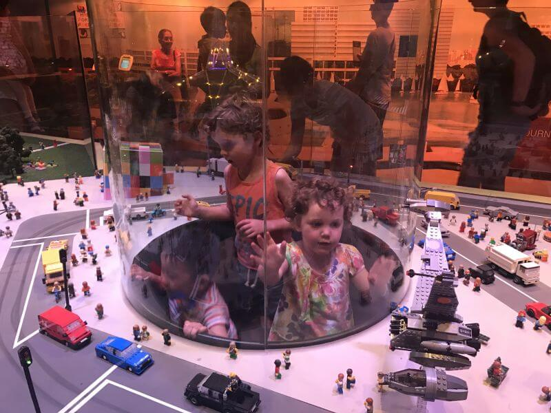 Ned and Olive from Hill Tribe Travels popping up in the clear globe to see the Lego mini exhibition closer