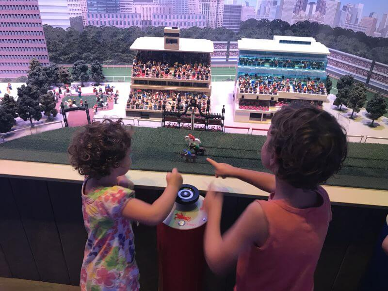 Ned and Olive from Hill Tribe Travels racing their horses along the Flemington Racecourse track in Miniland, Legoland Discovery Centre
