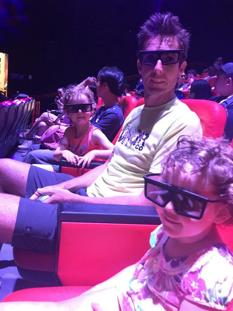 Ross, Ned and Olive from Hill Tribe Travels sitting in the cinema with their 3D glasses on waiting for the 4D movie to start