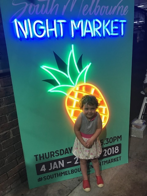 Olive standing in front of the sign advertising the South Melbourne Night Market