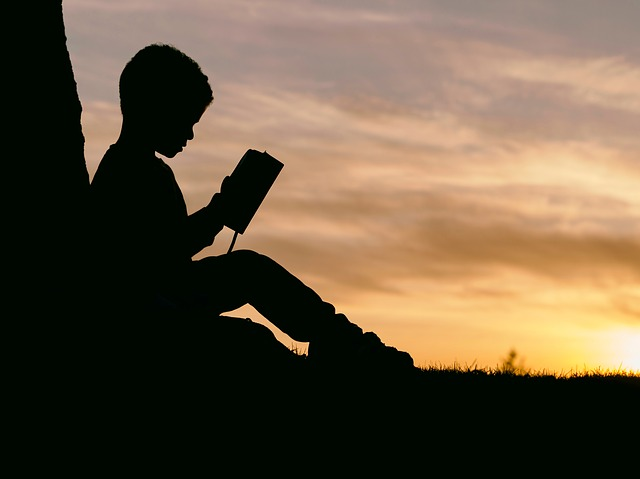 Kid reading a book in the sunset. Hill Tribe Travels always has books on holidays