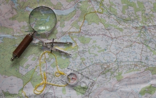 Ultimate Family Camping Packing List - image of a map, magnifying glass and compass - feature image for Hill Tribe Travels
