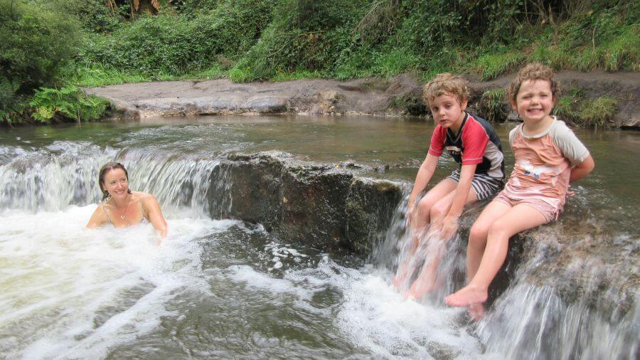 Hill Tribe Travels enjoying the hot water of Kerosene Creek whilst in Rotorua with kids