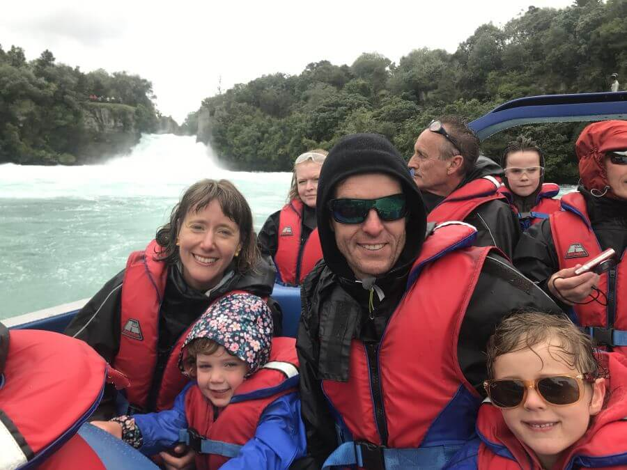All smiles on the HukaJet boat ride. Hill Tribe Travels, tour of New Zealand with kids. Huka Falls in the background