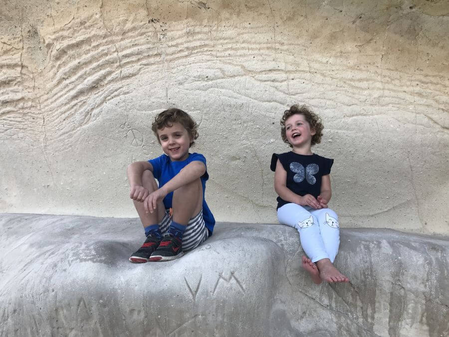 Ned and Olive from Hill Tribe Travels at Cathedral Cove sitting on a rock smiling together