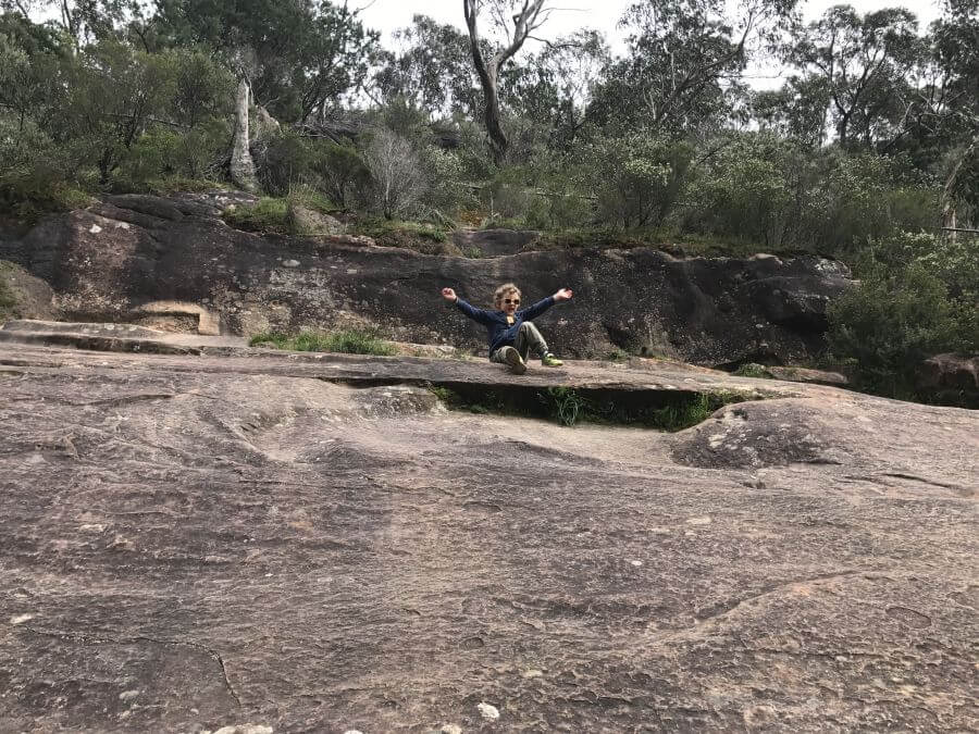 Ned from Hill Tribe Travels sitting at the top of some rocks at Venus Baths. A great walk for kids in The Grampians