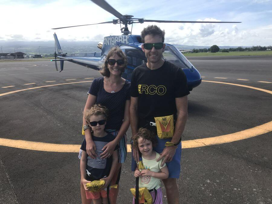 Hill tribe Travels standing in front of the helicopter they went on on The Big Island to view the lava