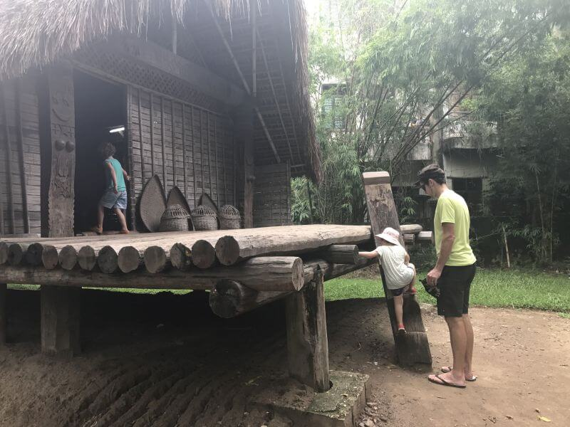 Climbing up into one of the display houses at the Museum of Ethnology in Hanoi Vietnam. The museum of Ethnology water puppet show is also shown amongst the houses