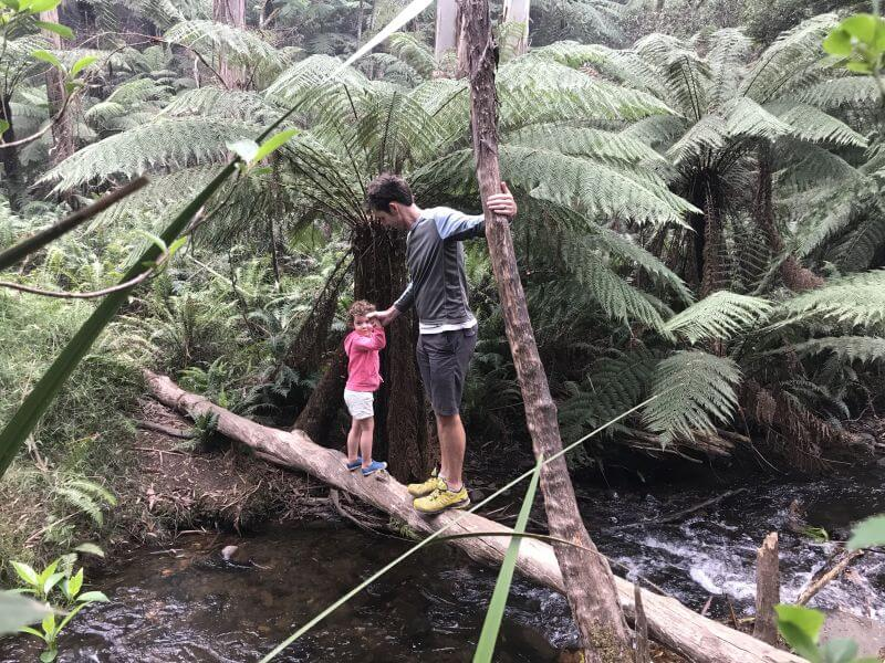 Olive and Ross from Hill Tribe Travels playing on a log over Cement Creek at the Redwoods Forest Warburton