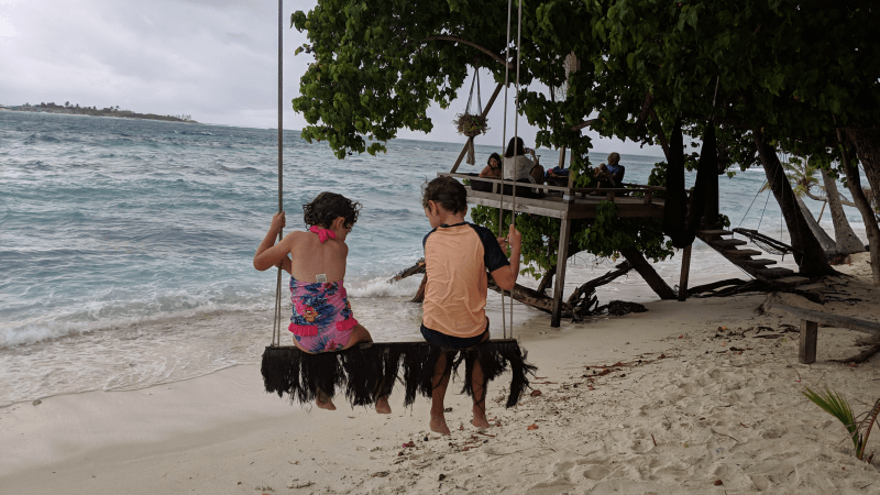 Ned and Olive from Hill Tribe Travels enjoying a swing along the beach on Thulusdhoo Island. Overcast and stormy day. Budget Maldives. Family friendly Maldives. Maldives on a budget.