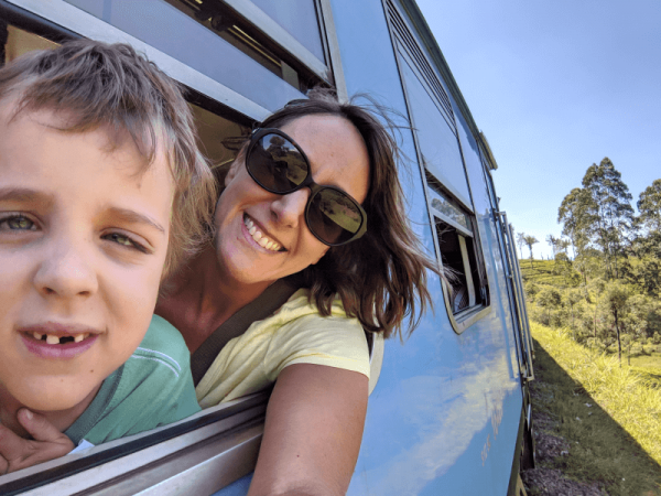 Ned and Amber with heads out of the window of the blue train from Ella to Kandy. Iconic Sri Lanka train trip