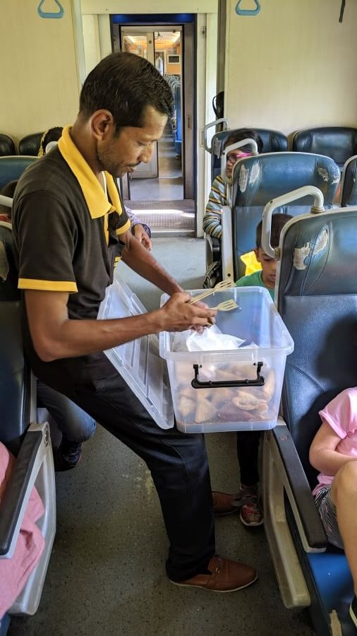 Staff member from the catering team selling snacks on the train from Ella to Kandy