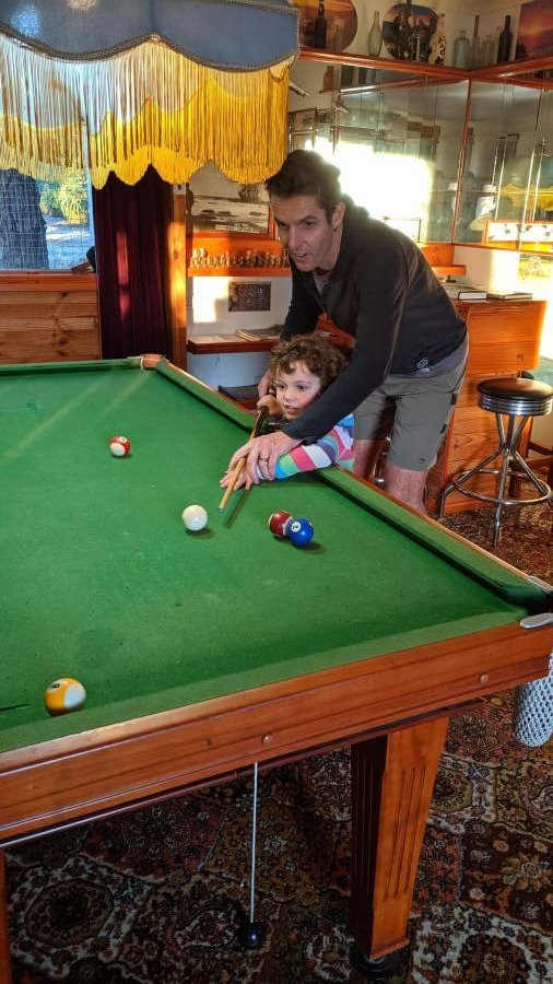Ross and Olive playing pool on the pool table in the games room at Cobden Crest Cottage
